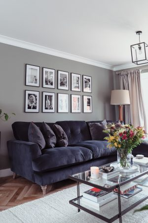 Black and white gallery wall of photographs in a new build green living room